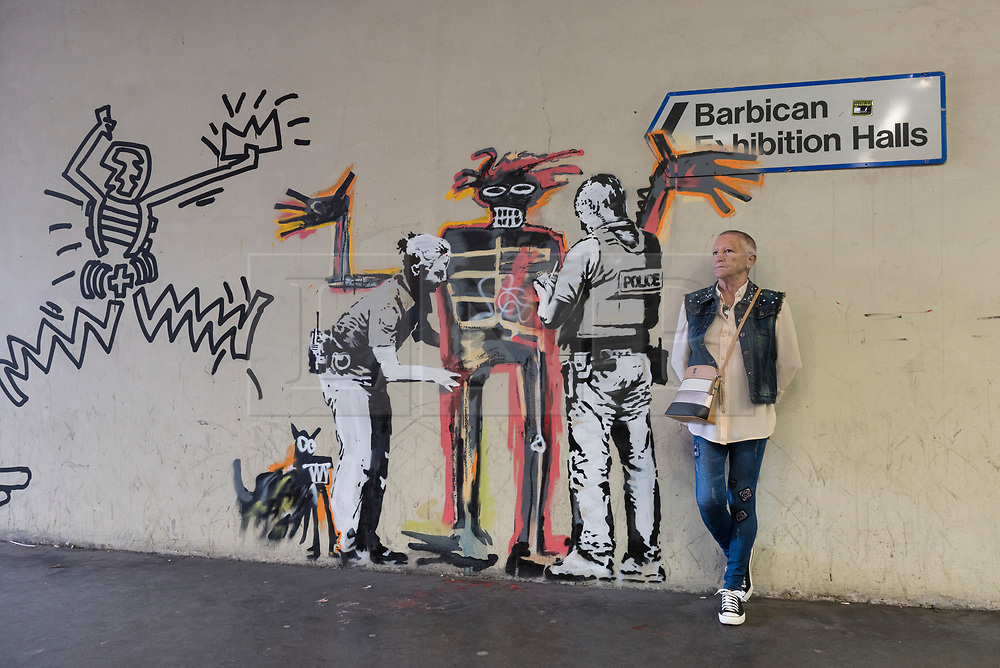 "© Licensed to London News Pictures. 20/09/2017. London, UK. A tourist poses with a new artwork outside the Barbican Art Gallery by street artist Bansky which references Jean-Michel Basquiat.  Preview of ""Basquiat: Boom for Real"", the first large-scale exhibition in the UK of the work of American artist Jean-Michel Basquiat (1960-1988) taking place at the Barbican Art Gallery, 21 September-28 January 2018. Photo credit : Stephen Chung/LNP"