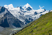 """The icy Bernina Range rises above Ova da Roseg river valley, near Pontresina, Switzerland, in the Bernina Alps, Europe. Roseg Glacier flows from Piz Glüschaint (3594 m). Val Roseg is in the Swiss canton of Graubünden (or Grisons / Grigioni / Grischun); the lower Roseg Valley is in Pontresina, whereas the upper valley is in an exclave of Samedan Municipality. Hike from Pontresina up Roseg Valley to Fuorcla Surlej for stunning views of Piz Bernina and Piz Roseg, finishing at Corvatsch Mittelstation Murtel cable car. Walking 14 km, we went up 1100 meters and down 150 m. Optionally shorten the hike to an easy 4 km via round trip lift. The Swiss valley of Engadine translates as the """"garden of the En (or Inn) River"""" (Engadin in German, Engiadina in Romansh, Engadina in Italian), and is part of the Danube basin."""