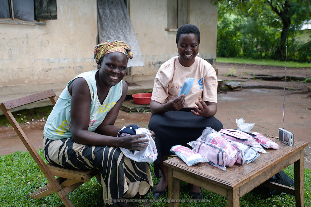 """Lovisa Wankya (right), a teacher and an Afripads dealer, in front of her home near Tororo in Eastern Uganda, explaining how Afripads work to Caroline Adongo on 1 August 2014. Having heard of Afripads and """"Madam Wankya"""" on the radio, Caroline was interested in them, but didn't know how to contact Lovisa. She happened to be passing by, and was excited to meet """"Madam Wankya"""" and learn about Afripads. She decided to buy two kits, one for herself and one for her daughter. (Afripads are reusable fibre sanitary pads that are having a revolutionary impact on menstrual hygiene management, particularly amongst girls and women who cannot afford expesive disposable pads, and who previously had to use rags, cotton wool or toilet paper.)"""