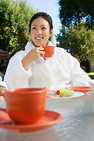 Young woman wearing bathrobe, drinking at outdoor table