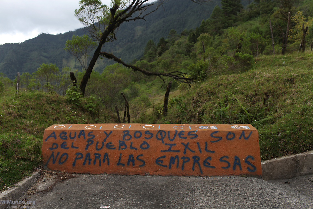 "Sign along the road in Nebaj reads: ""Water and Forests belong to the Ixil People, not the Corporations!"" The recent damming of rivers in order to build hydroelectric projects in the Ixil Mayan municipalities of Nebaj, Chajul and Cotzal, has caused rising conflicts in the war-torn region. Santa María Nebaj, Quiché, Guatemala. August 5, 2012."