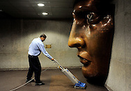 A worker vacuums near a replica of the face of the Statue of Liberty in the statue's visitors center in New York, New York, USA, on 20 May 2009.