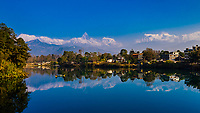The Annapurna Massif (range) of the Himalayas, which includes Annapurna 1, the tenth highest peak in the world and in center, Fishtail (Machpuchare) is reflected into Phewa Lake in the foreground, Pokhara, Nepal.