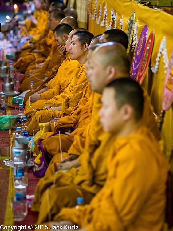 """21 DECEMBER 2015 - BANGKOK, THAILAND:  Buddhist monks lead prayers during the annual rededication of a Buddhist shrine in Pak Khlong Talat, also called the Flower Market. The market has been a Bangkok landmark for more than 50 years and is the largest wholesale flower market in Bangkok. A recent renovation resulted in many stalls being closed to make room for chain restaurants to attract tourists. Now Bangkok city officials are threatening to evict sidewalk vendors who line the outside of the market. Evicting the sidewalk vendors is a part of a citywide effort to """"clean up"""" Bangkok.      PHOTO BY JACK KURTZ"""