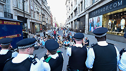 "© Licensed to London News Pictures. 19/04/2019. LONDON, UK.  Police officers block activists trying to run onto Regent Street ahead of the removal of the pink boat at Oxford Circus during ""London: International Rebellion"", on day five of a protest organised by Extinction Rebellion.  Protesters are demanding that governments take action against climate change.  Police have issued a section 14 order requiring protesters to convene at Marble Arch only so that the protest can continue.  Photo credit: Stephen Chung/LNP"
