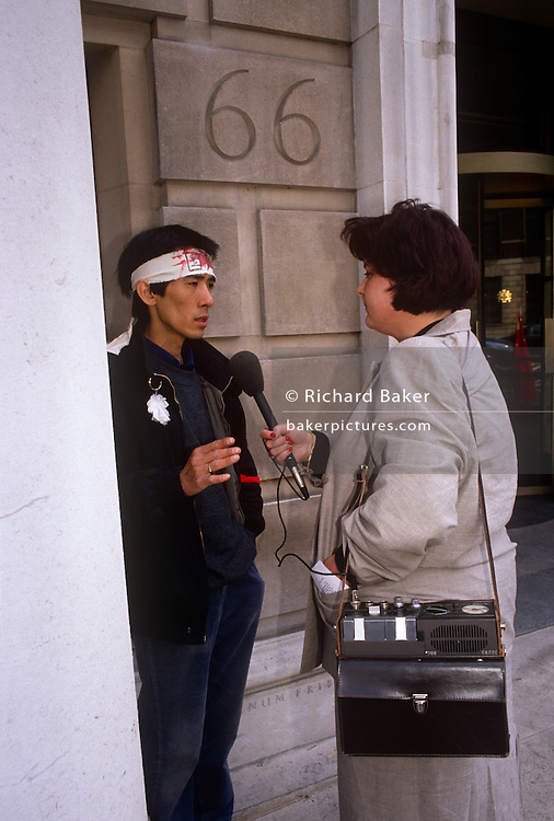 A Chinese exile is interviewed by a radio journalist opposite his embassy a day after the Tiananmen Sq massacre. Using old technology consisting of a tape recorder and analogue microphone, the reporter records the words of an activist, his words being broadcast, potentially across the world. The political crackdown that initiated on June 3–4 1989 became known as the Tiananmen Square Massacre as troops with assault rifles and tanks inflicted casualties on unarmed civilians trying to block the military's advance towards Tiananmen Square in the heart of Beijing, which student demonstrators had occupied for seven weeks.