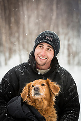 A man and his golden retriever on a snowy winter day in New Hampshire's White Mountains. Randolph Community Forest.