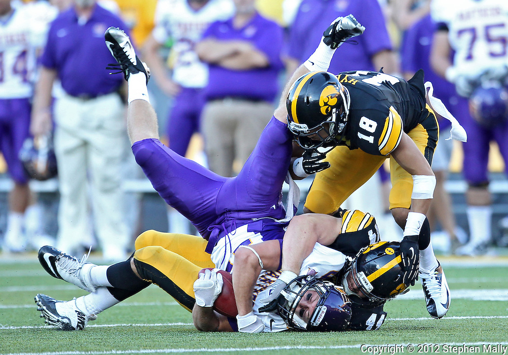 September 15 2012: Iowa Hawkeyes linebacker James Morris (44) drives Northern Iowa Panthers wide receiver Chad Owens (19) into the ground as cornerback Micah Hyde (18) closes in during the second half of the NCAA football game between the Northern Iowa Panthers and the Iowa Hawkeyes at Kinnick Stadium in Iowa City, Iowa on Saturday September 15, 2012. Iowa defeated Northern Iowa 27-16.