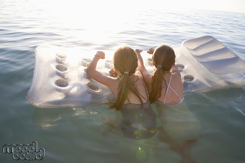 Twin sisters on air bed in evening light