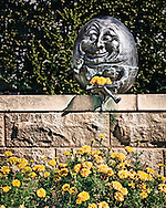 Someone had plucked three blooms from the marigolds and placed them on Humpty Dumpty's open book. That small gesture created a bond between the sculpture and the flowers.