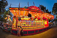 Aug. 25, 2012 - Middlebury, Connecticut, U.S. -  At the Water Gun Fun game booth. which is colorfully lit up at night, a family will try to win a stuffed toy prize, at Quassy Amusement Park. View taken with 180 degree fisheye lens.