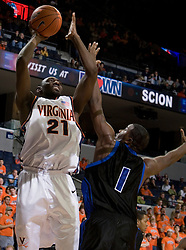 Virginia Cavaliers center Tunji Soroye (21) shoots over Longwood Lancers forward Clayton Morgan (1).  The Virginia Cavaliers Men's Basketball Team defeated Longwood University 90-49 at the John Paul Jones Arena in Charlottesville, VA on February 13, 2007.