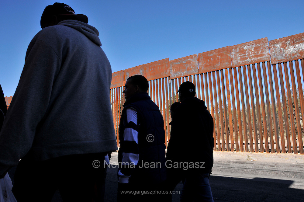 Men in Nogales, Sonora, Mexico, pass near the border wall where a US Border Patrol agent in Nogales, Arizona, shot and killed a 16-year-old youth who was allegedly throwing rocks across the border at the agent.