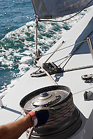 Sailor adjusting rope on boat close up of hand