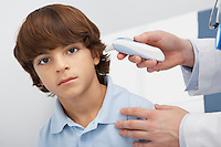 Boy having temperature taken with ear thermometer,portrait