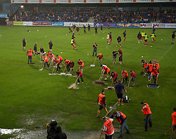 ALTACH, AUSTRIA - Saturday, July 17, 2010: Workers frantically try and remove water from the pitch as Liverpool's players warm-up before the first preseason match of the 2010/2011 season at the Cashpoint Arena. (Pic by David Rawcliffe/Propaganda)
