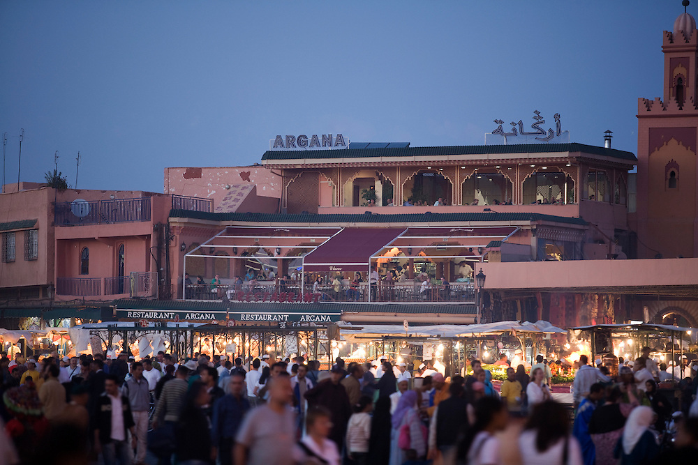 A restaurant overlooks a busy Djemaa el Fna at night as crowds stream by.