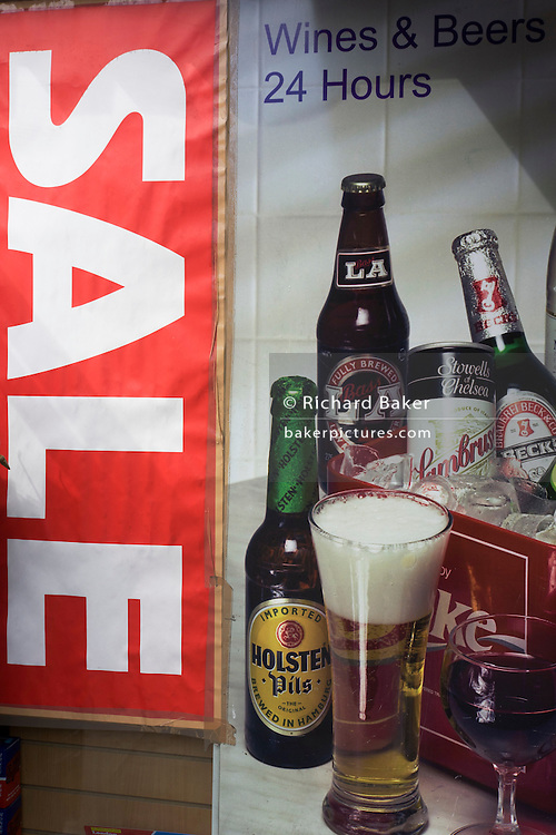 Sale sign and poster for alcoholic drinks like bottles of beer and glass of wine in a London off-license window.