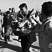 A father walks his wounded son to a medic tent in Mosul at a camp for internally displaced people in Khazir Camp in Northern Iraq.