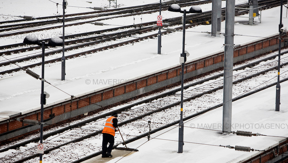 Train Guards clean snow of the platform at Edinburgh's Waverley Station. Heavy snow has fallen across large parts of the UK, disrupting travel and closing thousands of schools.  Weather warnings of heavy and drifting snow are also in place for many southern and eastern parts of Scotland.