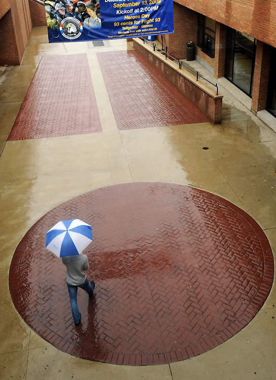 A student walks on the esplanade between the Kent Student Center and the Kiva on a rainy fall afternoon.<br /> <br /> Bob Christy<br /> September 2008<br /> vertical, student, esplanade, fall, autumn