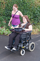 Woman with a disability going along the street chatting to her non disabled friend,