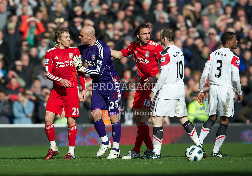 LIVERPOOL, ENGLAND - Sunday, March 6, 2011: Liverpool's Lucas Leiva is pulled away by team-mates goalkeeper Jose Reina and Sotirios Kyrgiakos after suffering a horrific challenge from Manchester United's Rafael Da Silva (not in frame) and being abused by Wayne Rooney during the Premiership match at Anfield. (Photo by David Rawcliffe/Propaganda)