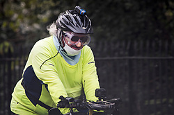 © Licensed to London News Pictures. 04/04/2020. London, UK. A cyclist wearing goggles and a face mask at Regents Park in London, during a pandemic outbreak of the Coronavirus COVID-19 disease. The public have been told they can only leave their homes when absolutely essential, in an attempt to fight the spread of coronavirus COVID-19 disease. Photo credit: Ben Cawthra/LNP