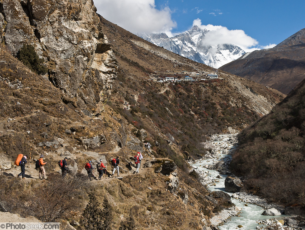 Trekkers hike towards the village of Pangboche, towards the mountain of Lhotse (27,940 feet), the world's fourth highest peak, Nepal. The tremendous south face of Lhotse rises 2 vertical miles in a steep slope averaging a 55 degree angle. Sagarmatha National Park was created in 1976 and honored as a UNESCO World Heritage Site in 1979.