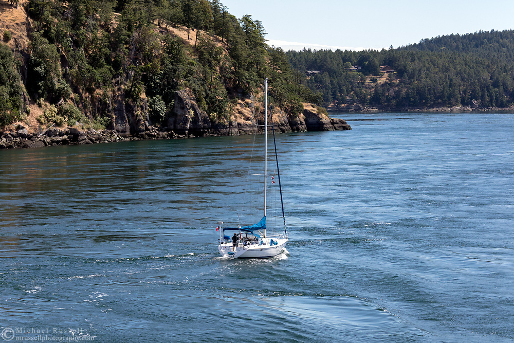 A sailboat makes its way through Active Pass between Galiano Island and Mayne Island in British Columbia's Gulf Islands.