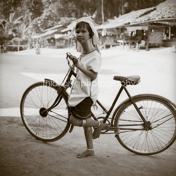 Portrait of Padong (long neck) village girl with neck rings and her bike, Burmese refugee camp, Western Thailand