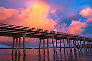 Rainbow and firey clouds over the bridge crossing the bay at Lover's Key, Florida, USA.