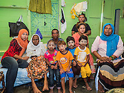 02 JUNE 2015 - KULAI, JOHORE, MALAYSIA: ASMA, 90 years old, (second from left) a Rohingya refugee from Sittwe, Myanmar, with her family in her home in Kulai. She came to Malaysia on a boat with 50 members of her extended family. They paid traffickers 250,000 Malaysian Ringgits (about $65,000 US) to bring them to Malaysia via traffickers' camps in Thailand. The UN says the Rohingya, a Muslim minority in western Myanmar, are the most persecuted ethnic minority in the world. The government of Myanmar insists the Rohingya are illegal immigrants from Bangladesh and has refused to grant them citizenship. Most of the Rohingya in Myanmar have been confined to Internal Displaced Persons camp in Rakhine state, bordering Bangladesh. Thousands of Rohingya have fled Myanmar and settled in Malaysia. Most fled on small fishing trawlers. There are about 1,500 Rohingya in the town of Kulai, in the Malaysian state of Johore. Only about 500 of them have been granted official refugee status by the UN High Commissioner for Refugees. The rest live under the radar, relying on gifts from their community and taking menial jobs to make ends meet. They face harassment from Malaysian police who, the Rohingya say, extort bribes from them.     PHOTO BY JACK KURTZ