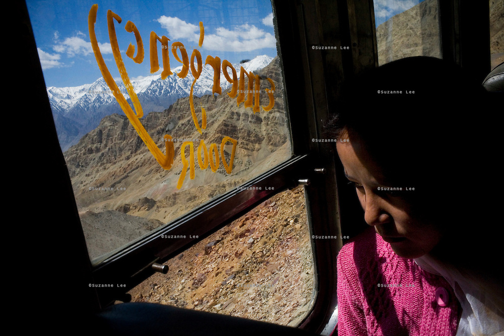 A Ladakhi girl looks out of the window on the bus on 3rd June 2009 on the way to Leh from Hemis and Ulley Valley, Ladakh, Jammu & Kashmir. The valley of Ladakh is located in the Indian Himalayas, in the northern state of Jammu and Kashmir. Photo by Suzanne Lee