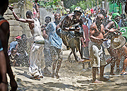 Members of a rara band splash water during a parade surrounding the Saut D'eau voodou festival in Ville Bonheur, Haiti.