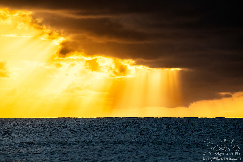 Crepuscular rays form as the late afternoon shines through holes in the clouds over Puerto Real off the coast of Esperanza on the island of Vieques, Puerto Rico.