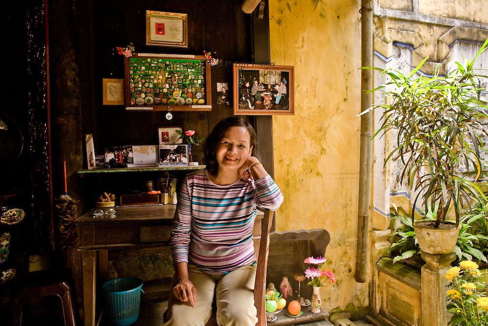 Portrait of a woman in her 40s seated in her house in Hoi An, an ancient structure built by her forbears in which she continues to live.  She is seated smiling at her desk; a glimpse into the interior courtyard beyond.  Soft golden light washes around her.