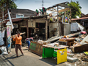 21 SEPTEMBER 2015 - BANGKOK, THAILAND: A demolition crew tears down a home near Wat Kalayanamit. Fiftyfour homes around Wat Kalayanamit, a historic Buddhist temple on the Chao Phraya River in the Thonburi section of Bangkok are being razed and the residents evicted to make way for new development at the temple. The abbot of the temple said he was evicting the residents, who have lived on the temple grounds for generations, because their homes are unsafe and because he wants to improve the temple grounds. The evictions are a part of a Bangkok trend, especially along the Chao Phraya River and BTS light rail lines. Low income people are being evicted from their long time homes to make way for urban renewal.    PHOTO BY JACK KURTZ