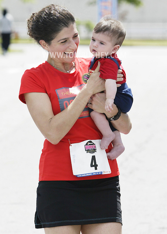 Judith Sambol of Manhattan holds her 5-month-old son Rueven Rosenbaum, who is wearing her medal, after winning the JRunners 5K Run Walk for Women at Sullilvan County Community College in Loch Sheldrake on Wednesday, July 27, 2011.