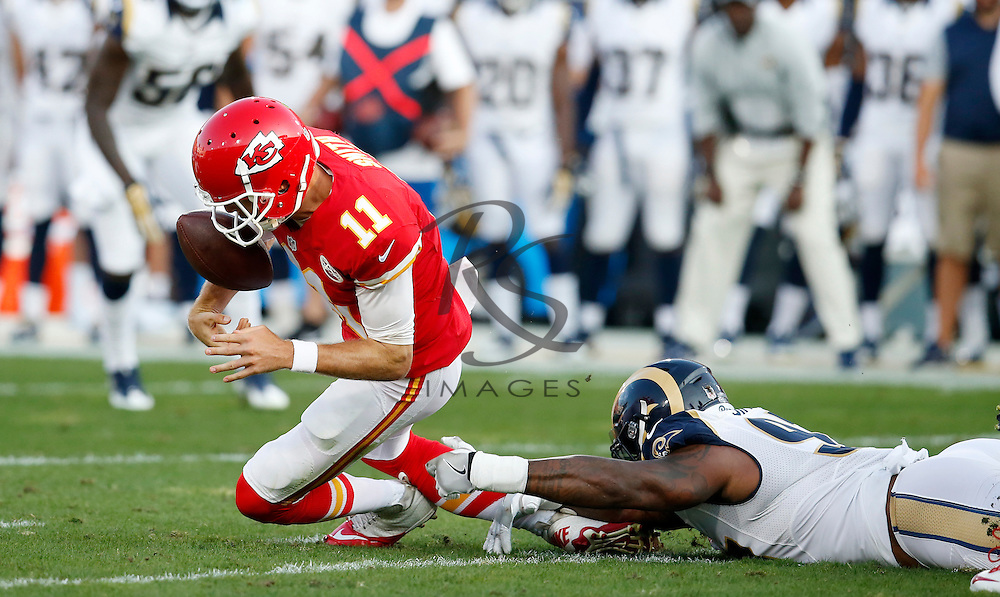 Kansas City Chiefs quarterback Alex Smith, left, fumbles the ball as he is taken down by Los Angeles Rams defensive end Eugene Sims during the first half of a preseason NFL football game, Saturday, Aug. 20, 2016, in Los Angeles. Smith recovered the fumble. (AP Photo/Rick Scuteri)