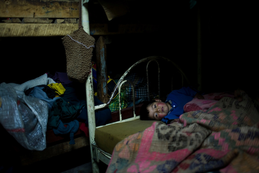 A child with lead poisoning lays in his bed.  His three siblings also have lead poisoning and there house is just across the river from the Doe Run Peru metal processing plant.