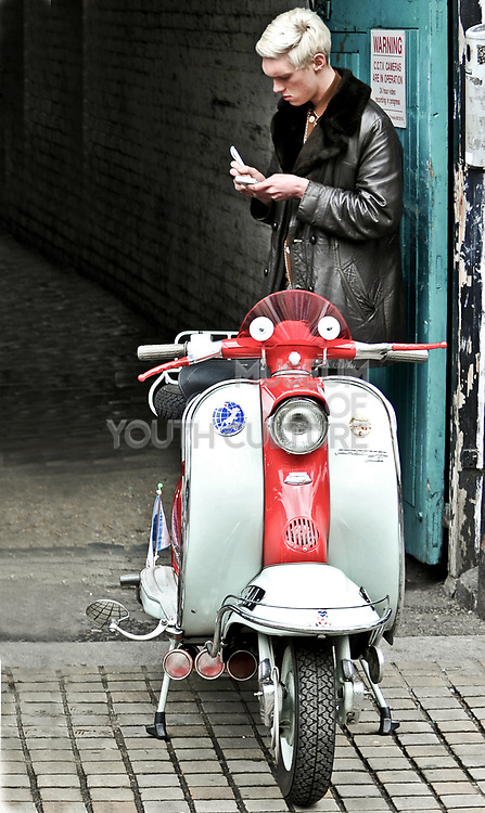Mod standing behind a red/white scooter, London, UK, 2010