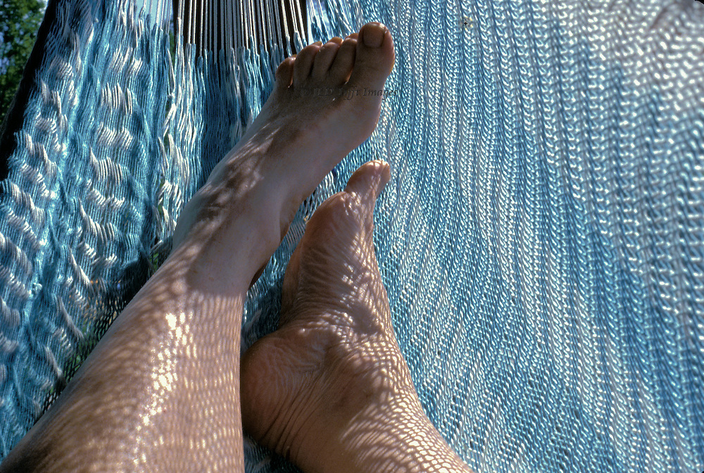 Relaxing in a hammock on a sunny day.  The texture of the open-weave hammock casts a network of shadows on my bare legs and ankles.