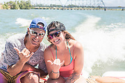 "Guy and girl smiling and giving the ""hang loose"" hand sign while riding in jet boat on the Snake River in Burley, Idaho."