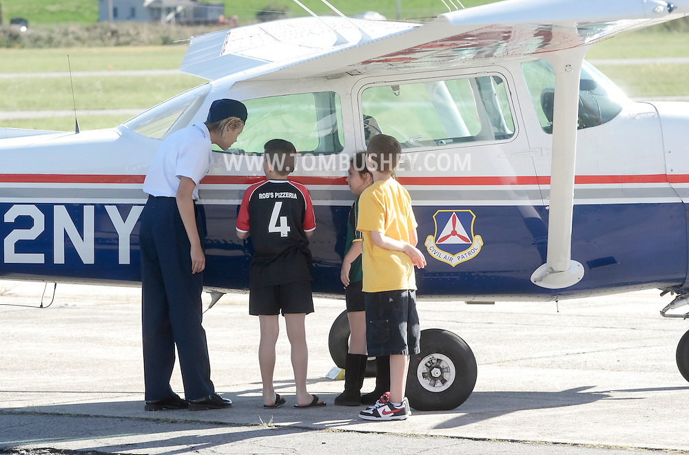 Montgomery, New York - A female member of the Civil Air Patrol's Cadet Program shows a girls and two boys a Civil Air Patrol airplane at Orange County Airport on Oct. 2, 2010.