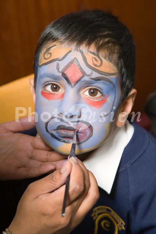 Teacher painting the face of a pupil at the Nottingham Islamia school Eid Fair,