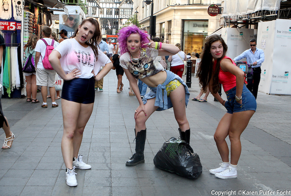 Citizens and visitors to England have been awaiting the delivery of the royal baby. Three women play around with a tourist near Oxford Circus recently.