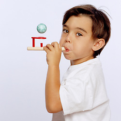 Boy Blowing into Blow Pipe and Ball Toy
