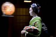 Miehina, a 20 year old maiko ( an apprentice geisha) from the Miyagawacho district of Kyoto, makes her way through the streets to her evening appointment with clients in a tea house, Japan, Sunday, May 18th 2008. The lantern hangs outside of a tea house, and is decorated with the traditional inter-twined red rings motif which signifies the Miyagawacho district.
