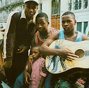 Group of teenagers and a little boy sitting in the street in Paris playing a guitar